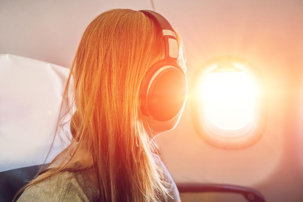 woman in airplane, overcoming fear of flying with meditation