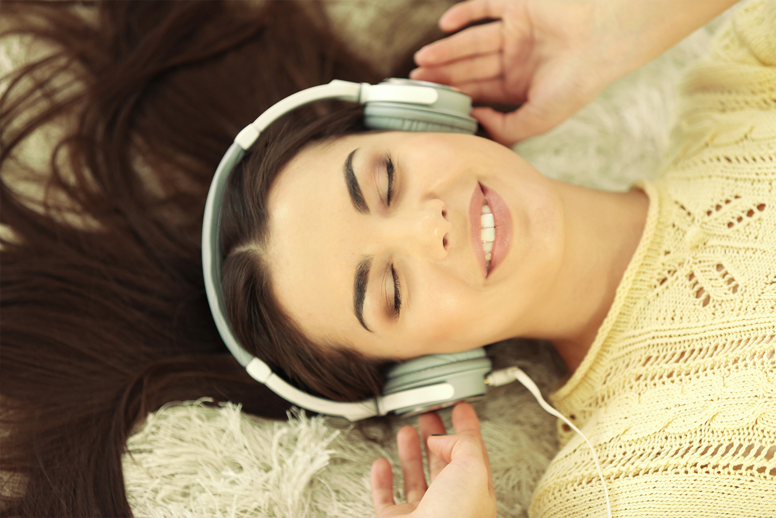 woman listening to synctuition with headphones lying down