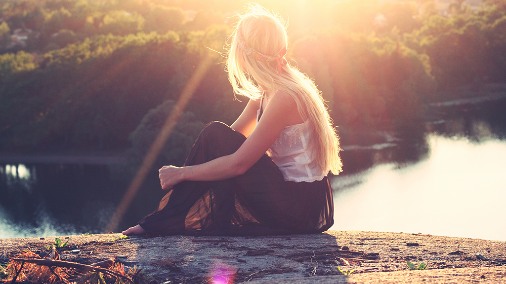 A young blonde woman, turning her back, looking at the sea sitting on the top of a hill