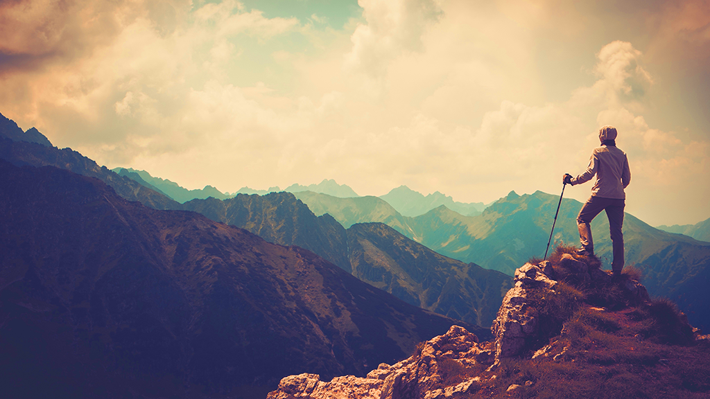 A man looking at the mountain scene, standing tall on a mountain, alone