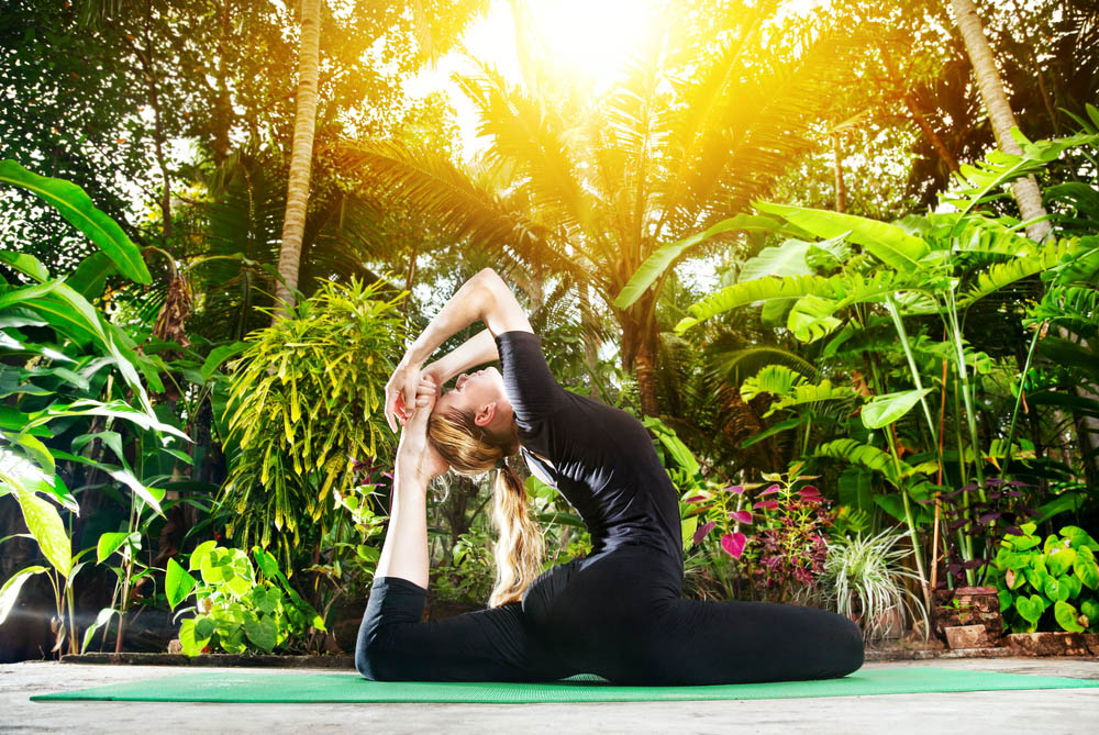 woman doing yoga pose with lush tropical landscape